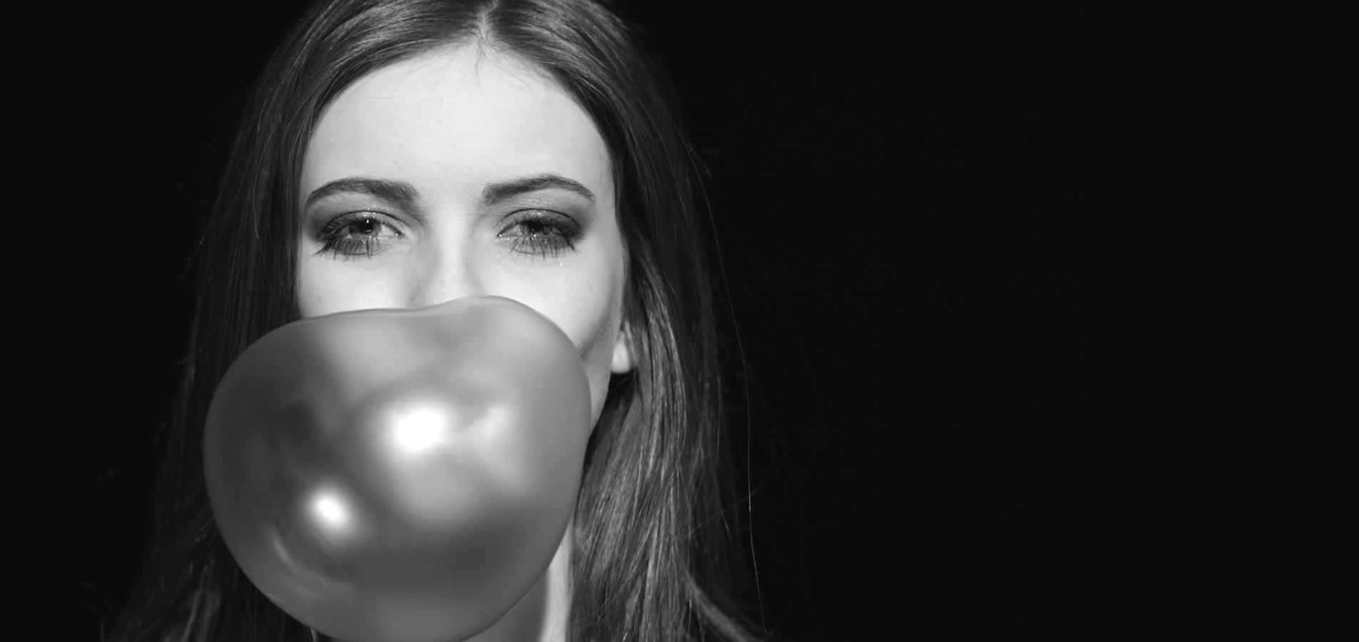 Jeune femme gonflant une bulle de chewing gum
